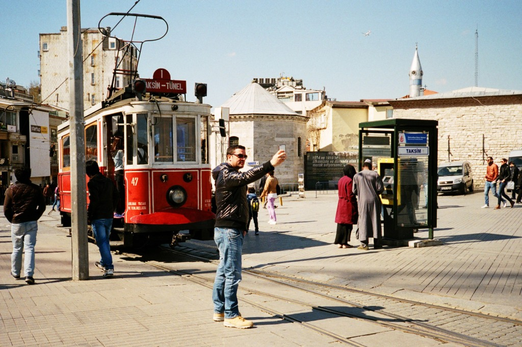 Historic tram passing through Taksim Square and İstiklal Avenue. It was common to see young boys jump onto the tram and hang on to the bars outside the tram for a free ride.